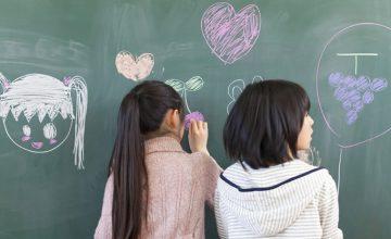 黒板に絵を書く小学生